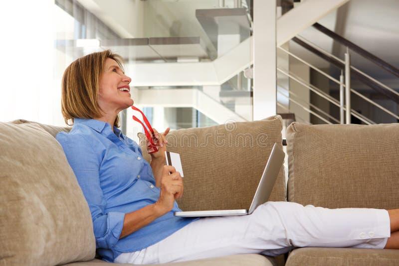 Glückliche ältere Frau, die auf Sofa mit Laptop und Kreditkarte sitzt lizenzfreie stockfotografie