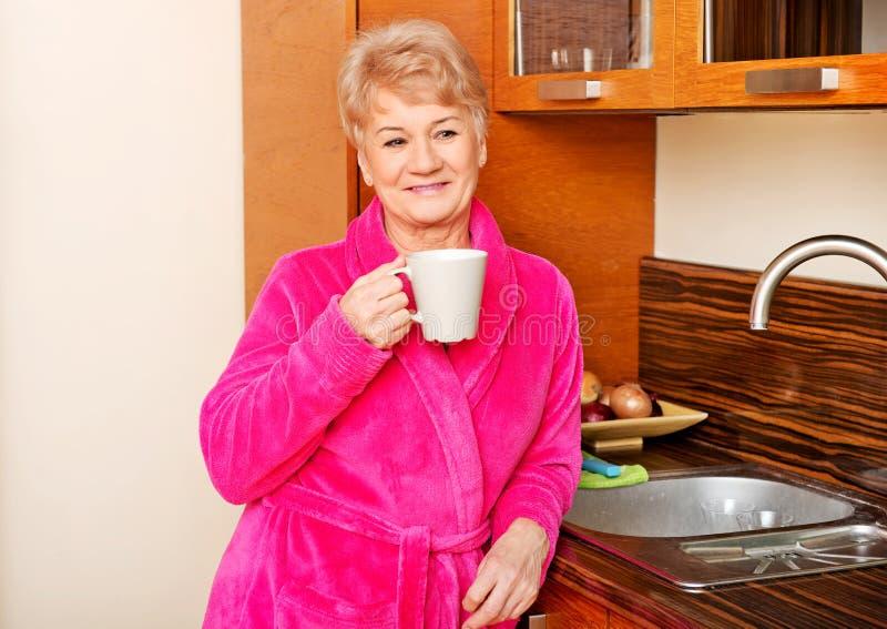 Glückliche ältere Frau, die in der Küche und trinkender Kaffee oder Tee steht stockbild