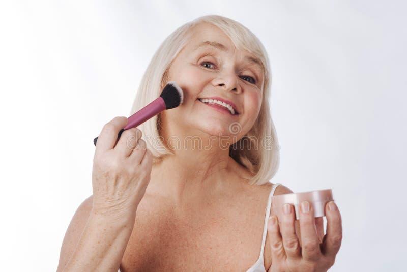 Glückliche ältere Frau, die eine kosmetische Bürste verwendet stockfotografie