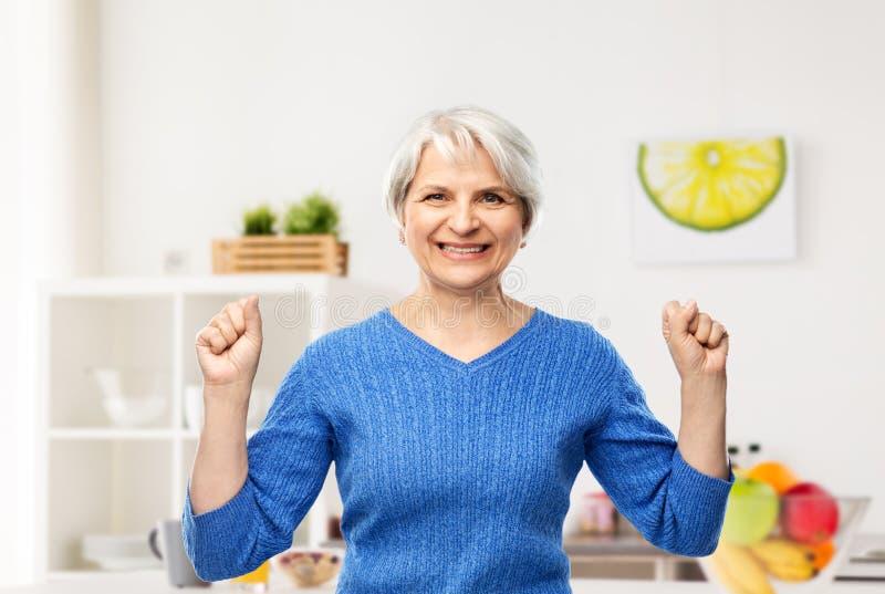 Glückliche ältere Frau, die Erfolg in der Küche feiert lizenzfreie stockfotos