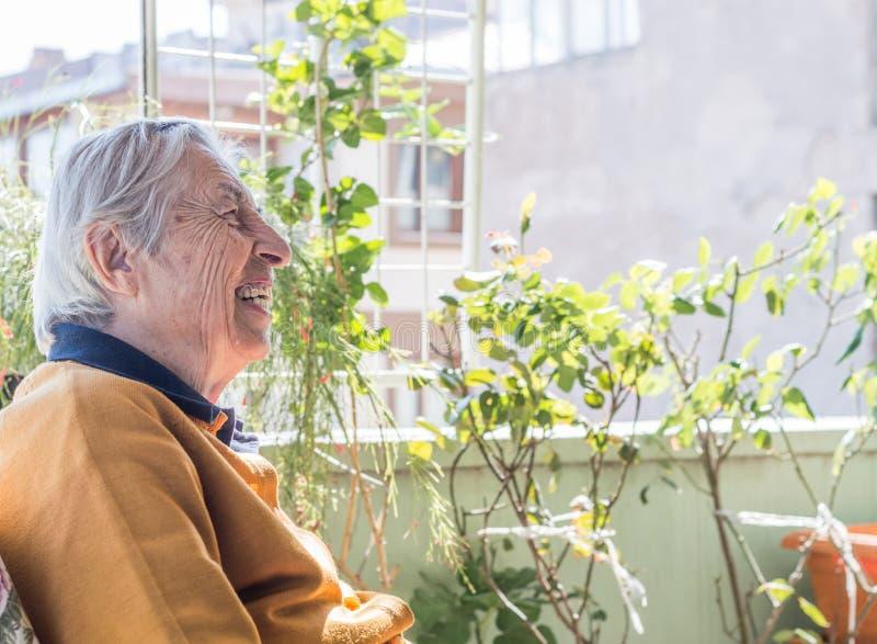 Glückliche ältere Frau, die im Balkon hat ein Gespräch mit ihrer Familie sitzt lizenzfreie stockbilder