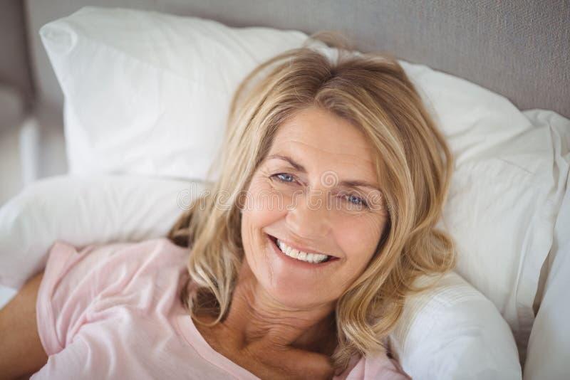 Glückliche ältere Frau, die im Bett liegt stockfotografie