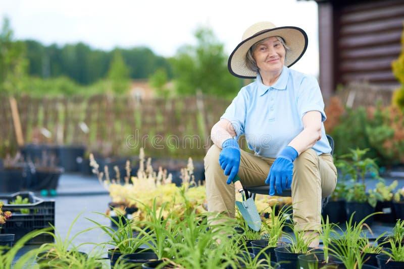 Glückliche ältere Frau, die im Garten aufwirft lizenzfreie stockbilder