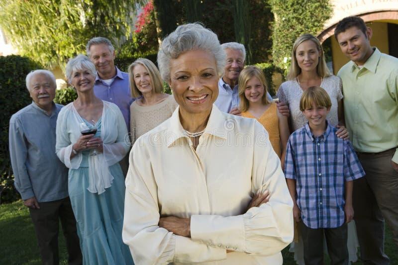 Glückliche ältere Frau, die mit den Händen gefaltet steht lizenzfreies stockfoto