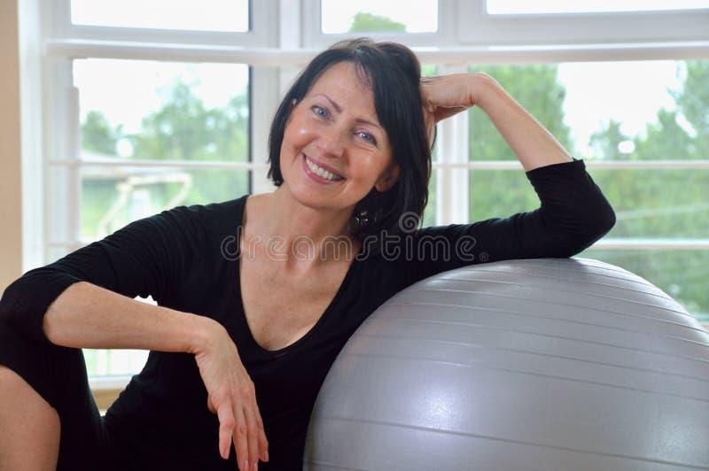 Glückliche ältere Frau, die nach Übung stillsteht stockfotos