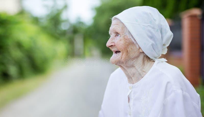 Glückliche ältere Frau, die oben draußen schaut stockbilder