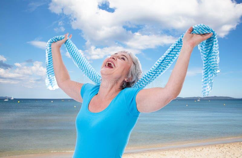 Glückliche ältere Frau, die oben ihre Hände ausdehnt stockfoto