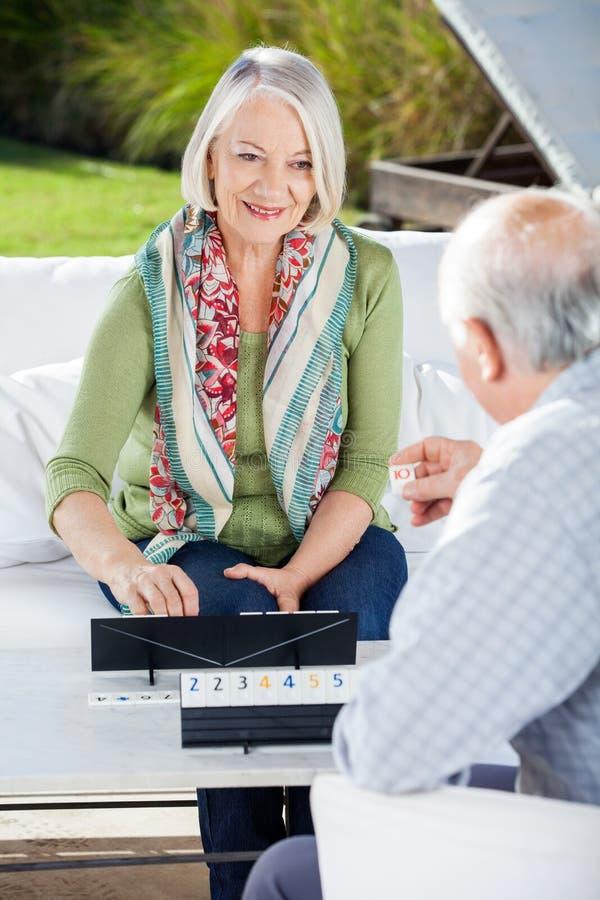 Glückliche ältere Frau, die Rummy With Man spielt stockbild