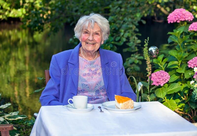 Glückliche ältere Frau, die Snäcke am Garten isst stockbild