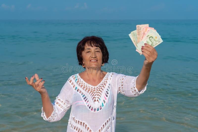 Glückliche ältere Frau, die viele Banknoten hält stockfoto