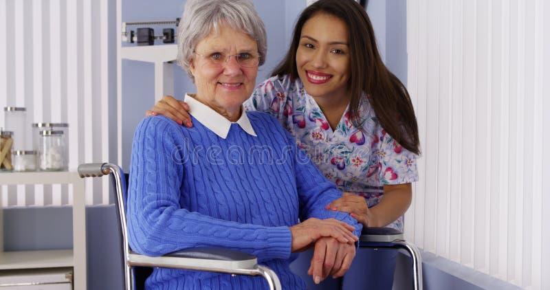Glückliche ältere Frau mit freundlicher mexikanischer Pflegekraft lizenzfreie stockfotografie