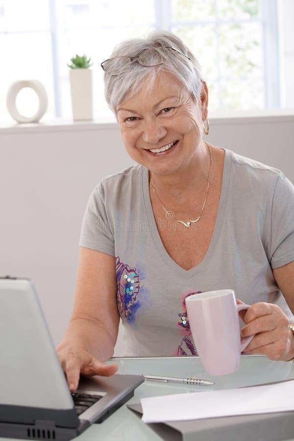 Glückliche ältere Frau mit Laptop stockfoto