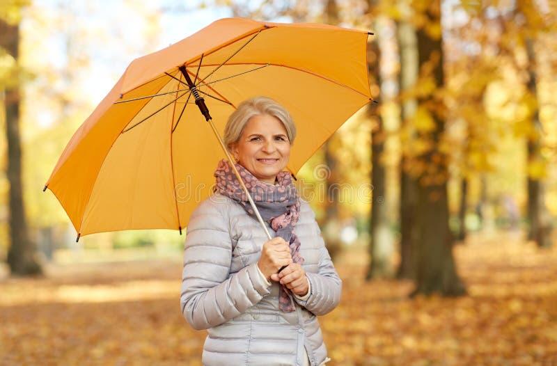 Glückliche ältere Frau mit Regenschirm am Herbstpark lizenzfreie stockbilder