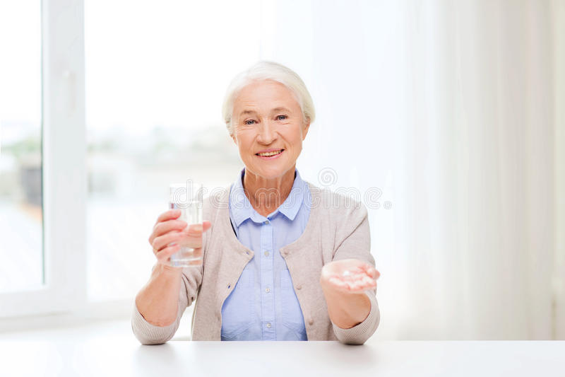 Glückliche ältere Frau mit Wasser und Medizin zu Hause stockfotos