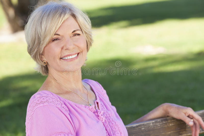 Glückliche ältere Frauen-sitzendes Außenseiten-Lächeln stockfotos