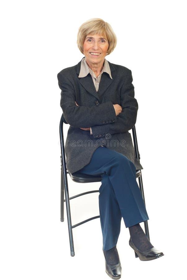 Glückliche ältere Geschäftsfrau auf Stuhl lizenzfreie stockbilder