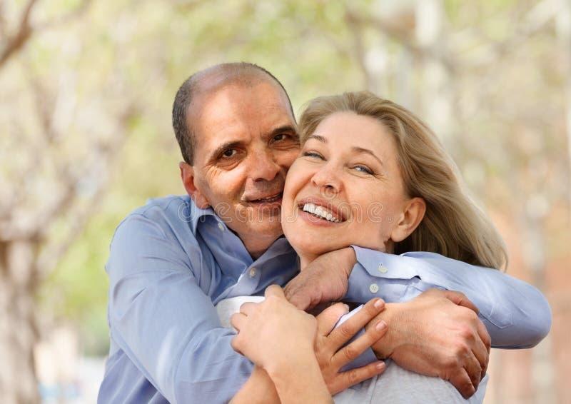 Glückliche ältere Liebhaber, die und das Lachen sich umarmen stockbilder