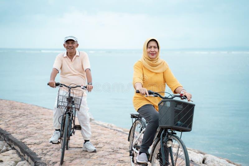Glückliche ältere moslemische Paare, die zusammen Reitenfahrrad ausüben lizenzfreie stockfotos