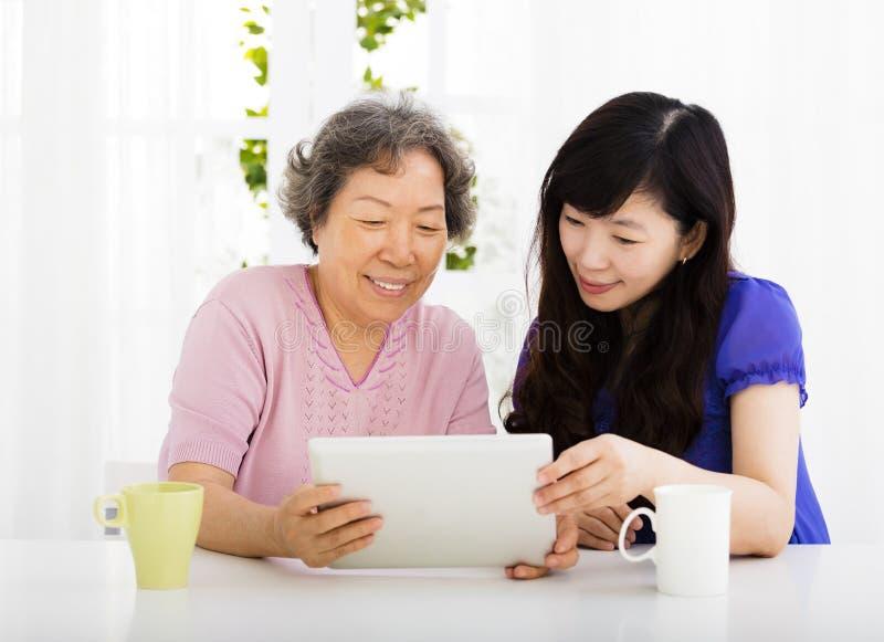 Glückliche ältere Mutter und Tochter, die Tabletten-PC lernt stockfotos