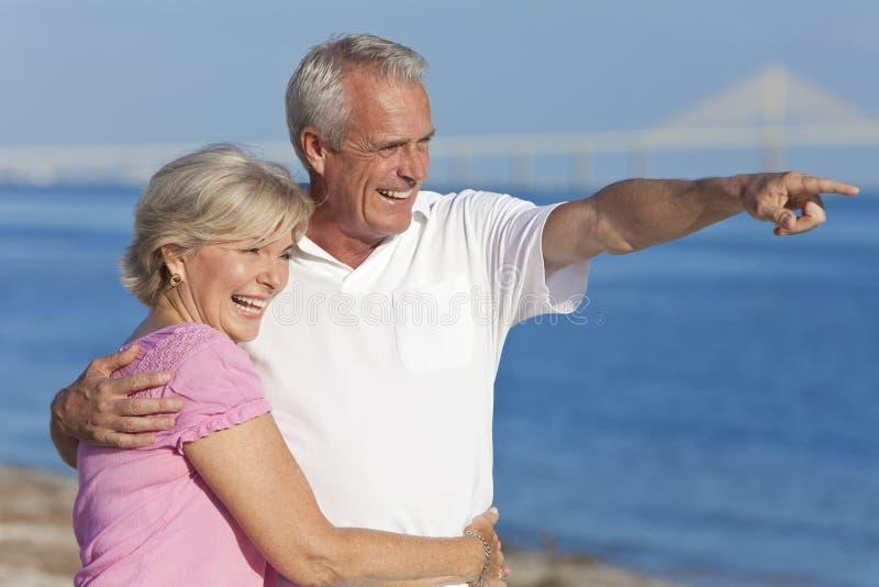 Glückliche ältere Paar-gehendes Zeigen auf Strand lizenzfreie stockfotografie