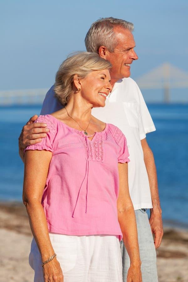 Glückliche ältere Paar-Stellung, die auf einem Strand umfasst stockbilder