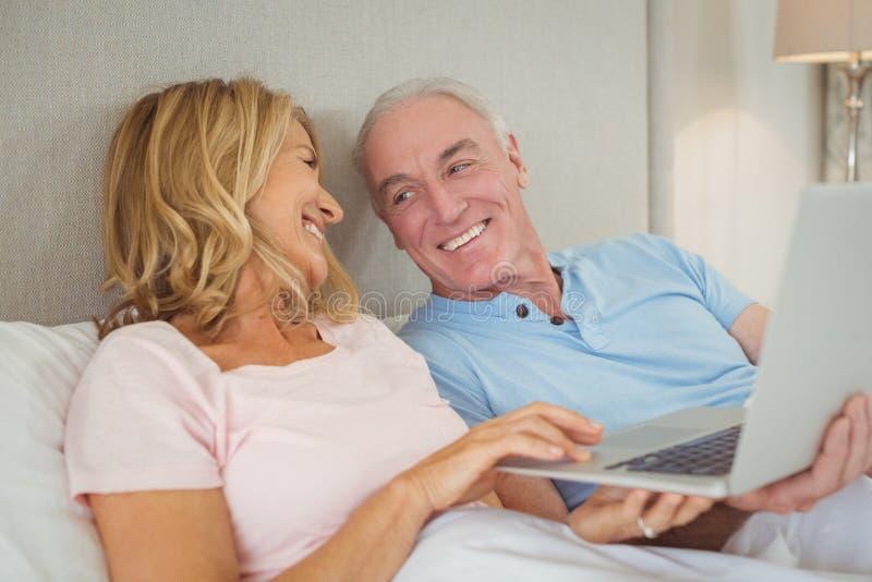 Glückliche ältere Paare auf Bett unter Verwendung des Laptops stockbilder