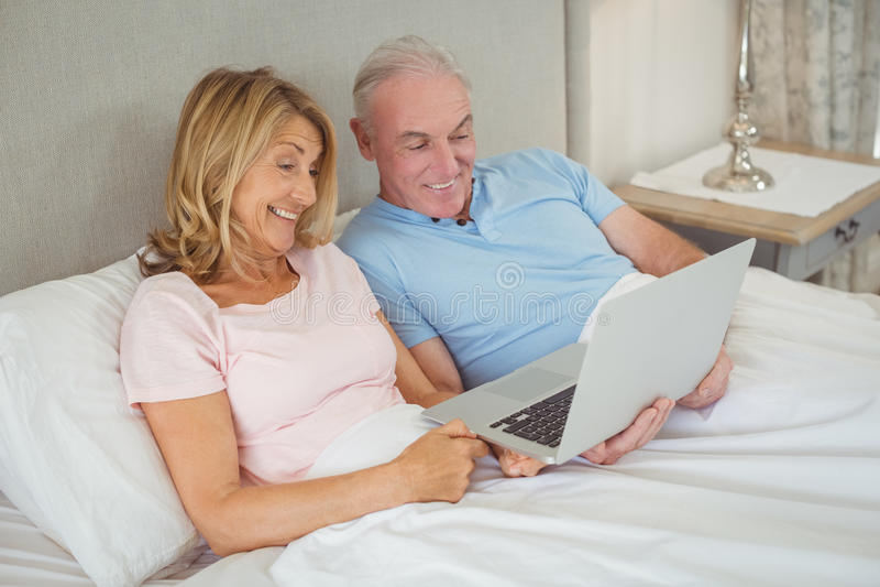Glückliche ältere Paare auf Bett unter Verwendung des Laptops lizenzfreie stockfotografie