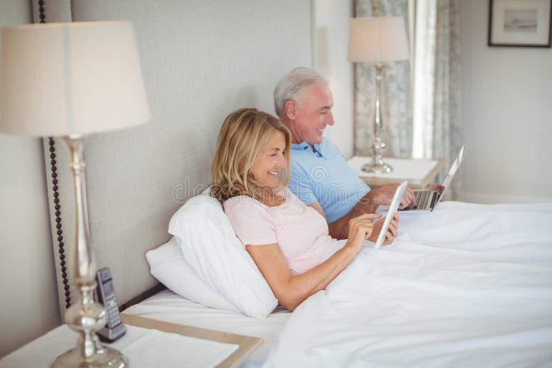 Glückliche ältere Paare auf Bett unter Verwendung des Laptops und der digitalen Tablette lizenzfreies stockfoto