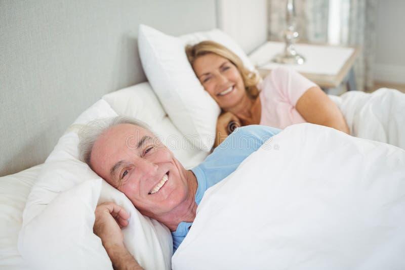 Glückliche ältere Paare, die auf Bett liegen stockfotos
