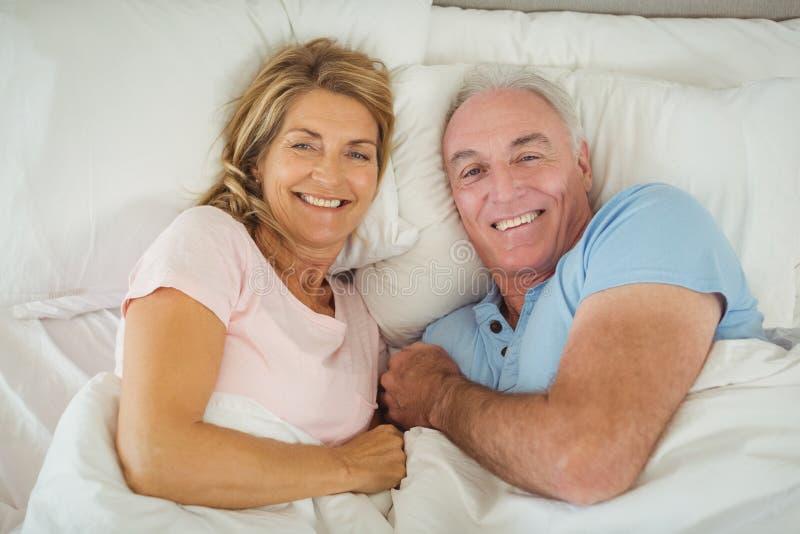 Glückliche ältere Paare, die auf Bett liegen lizenzfreies stockbild