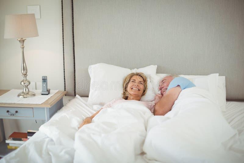 Glückliche ältere Paare, die auf Bett liegen lizenzfreie stockfotografie