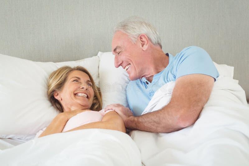 Glückliche ältere Paare, die auf Bett liegen stockbilder