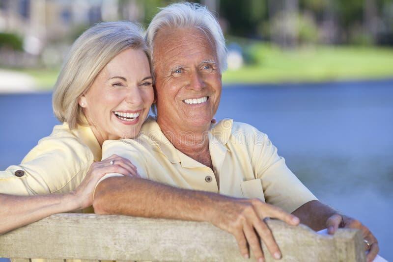 Glückliche ältere Paare, die auf dem Park-Bank-Lachen sitzen lizenzfreies stockfoto