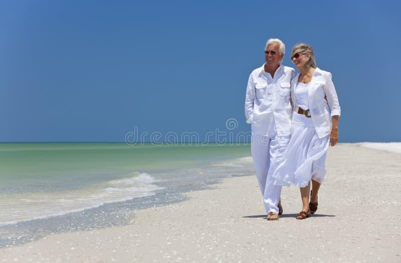 Glückliche ältere Paare, die auf einen tropischen Strand gehen lizenzfreies stockbild