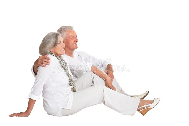 Glückliche ältere Paare, die auf weißem Hintergrund sitzen lizenzfreies stockfoto