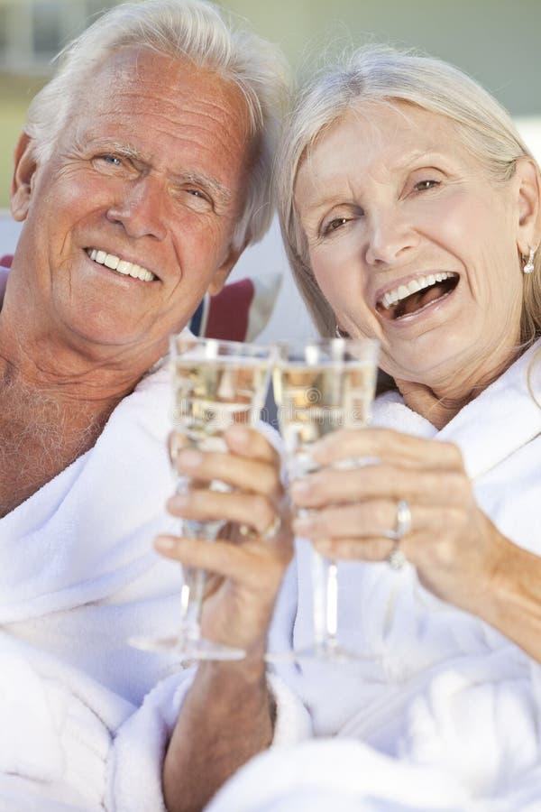 Glückliche ältere Paare, die Champagne-weißen Wein trinken stockfotografie