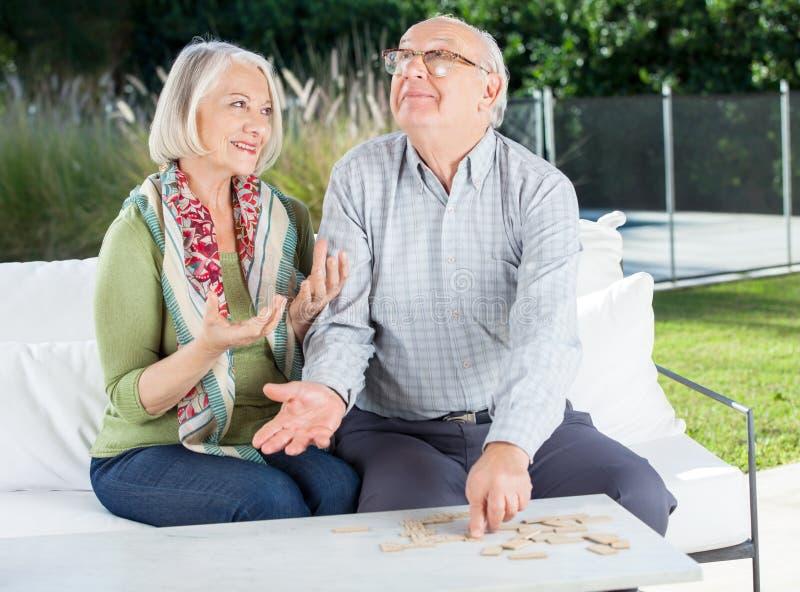 Glückliche ältere Paare, die Dominos an der Krankenpflege spielen stockfotos