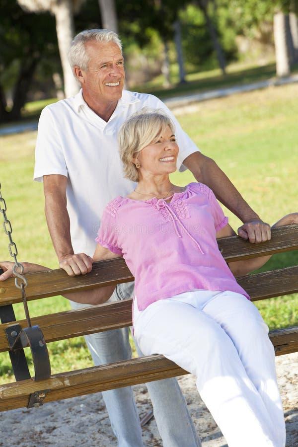 Glückliche ältere Paare, die draußen auf Park-Schwingen lächeln stockfotografie