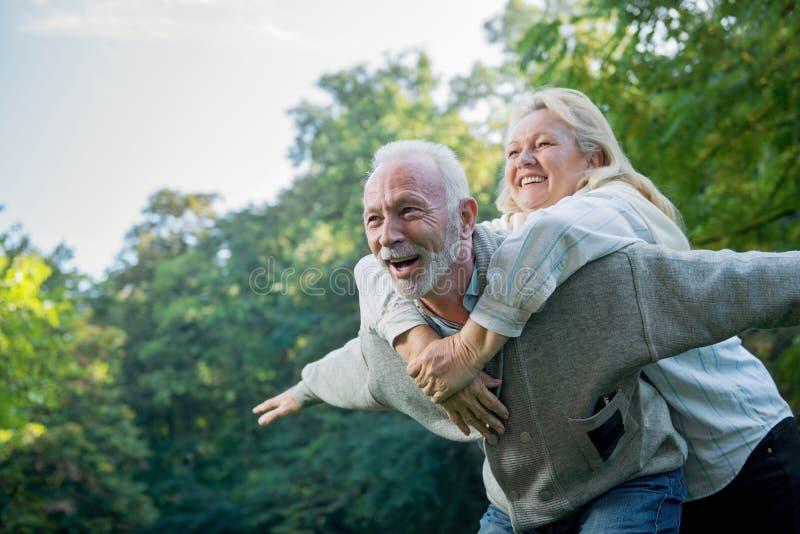Glückliche ältere Paare, die draußen in der Natur lächeln