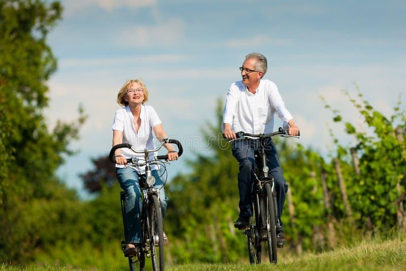 Glückliche ältere Paare, die draußen am Sommer einen Kreislauf durchmachen lizenzfreie stockfotos