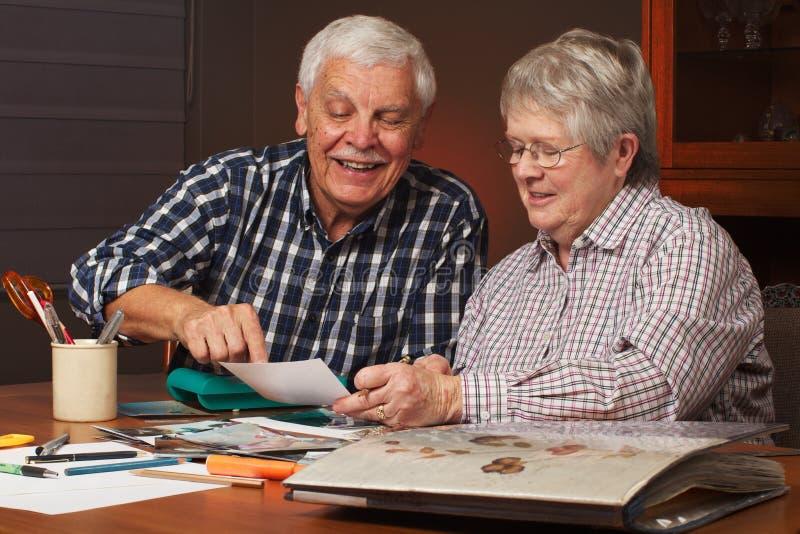 Glückliche ältere Paare, die ein Einklebebuch herstellen stockfotos