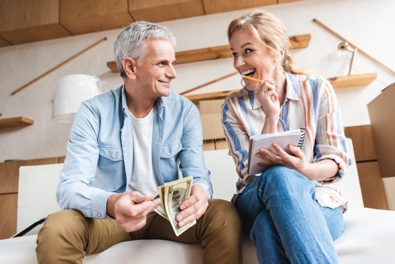 glückliche ältere Paare, die Geld zählen und wann lachen stockbild