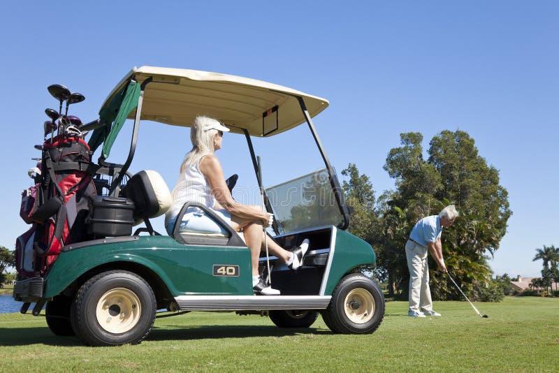 Glückliche ältere Paare, die Golf mit Wagen spielen lizenzfreie stockfotografie