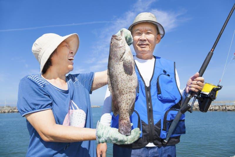 Glückliche ältere Paare, die großen Barsch fischen und zeigen stockfotos