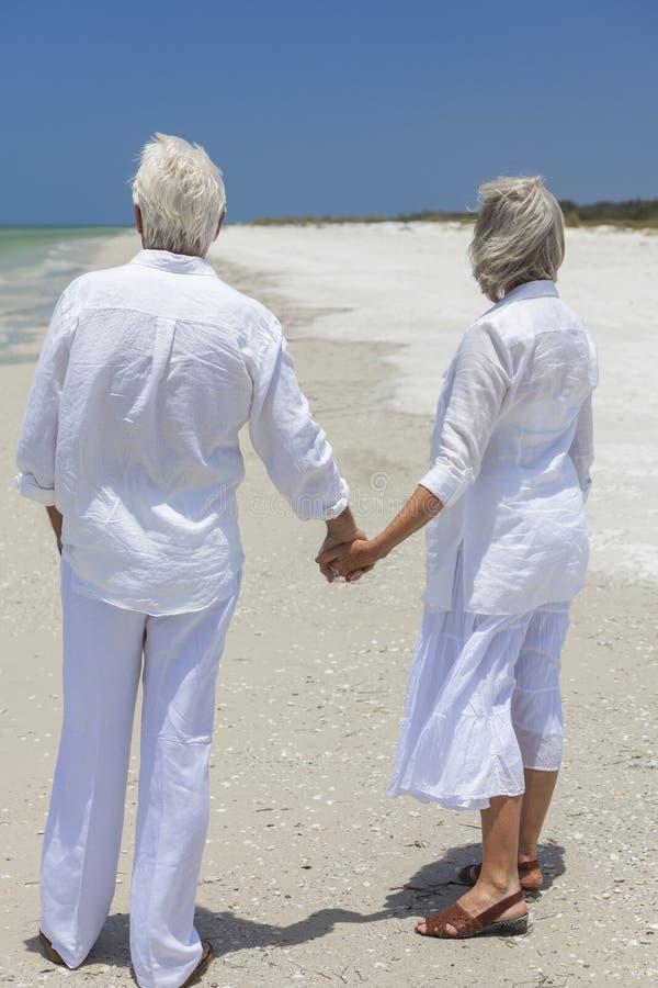 Glückliche ältere Paare, die Hände auf tropischem Strand anhalten lizenzfreies stockfoto