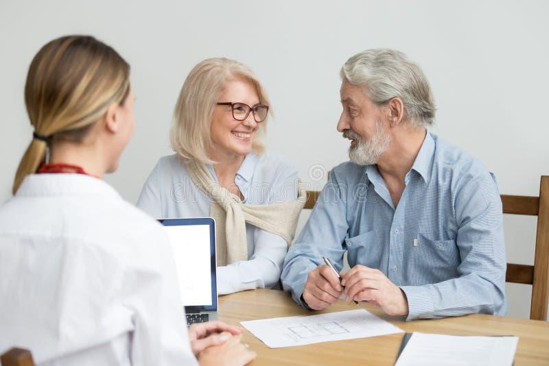 Glückliche ältere Paare, die Hauskauf bei der Sitzung mit AG besprechen lizenzfreie stockbilder