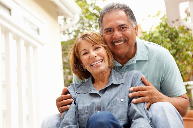 Glückliche ältere Paare, die im Garten sich entspannen lizenzfreie stockfotos