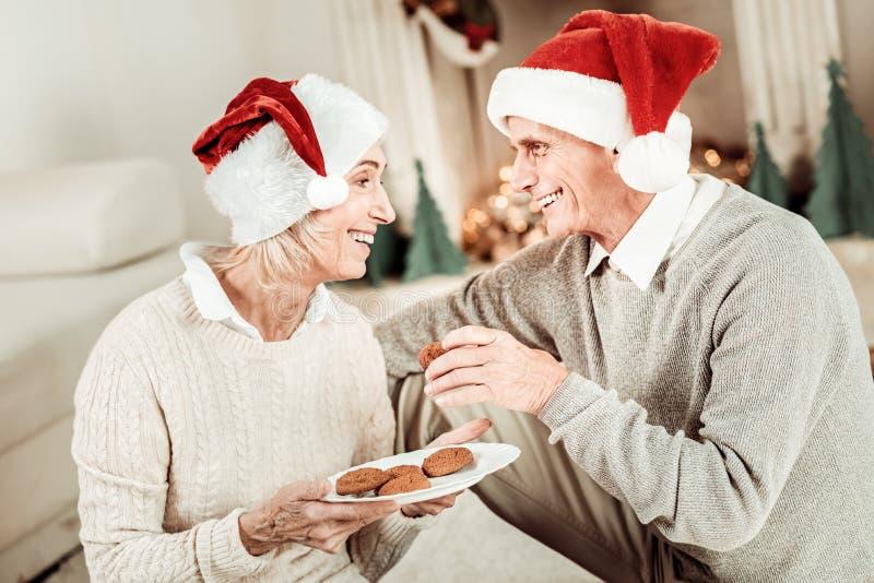 Glückliche ältere Paare, die Kuchen lächeln und essen stockfotos