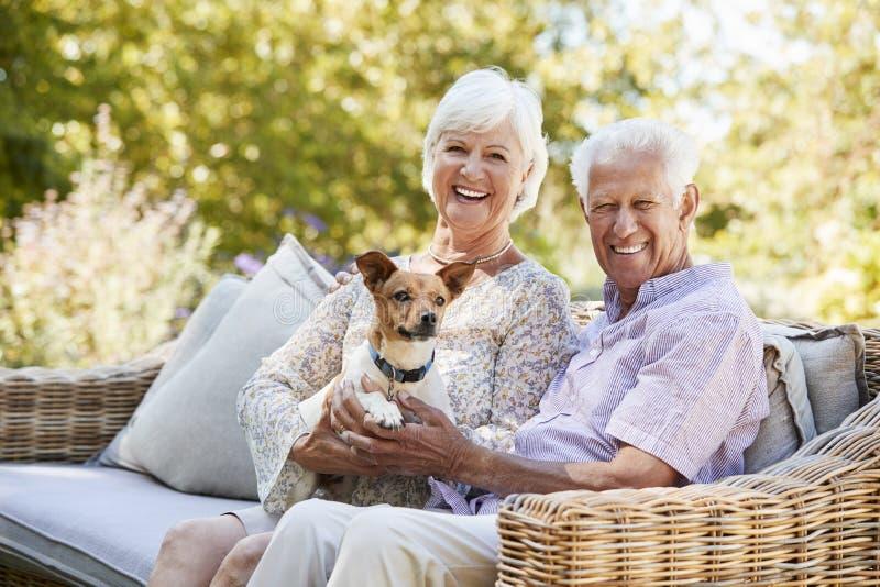 Glückliche ältere Paare, die mit einem Schoßhund im Garten sitzen stockbilder