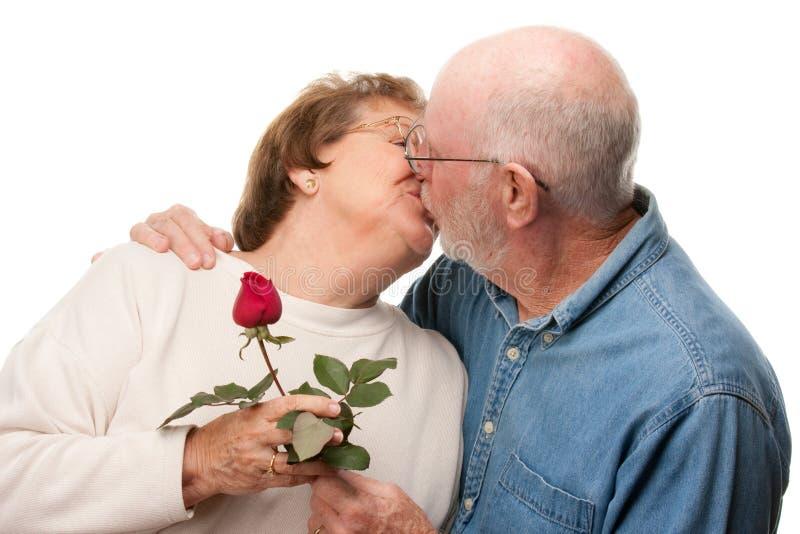 Glückliche ältere Paare, die mit roter Rose küssen lizenzfreies stockfoto